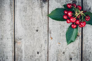 fresh red cherries on an old wooden table with green leaves, rustic style