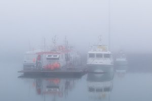 Fishing vessels in a foggy misty