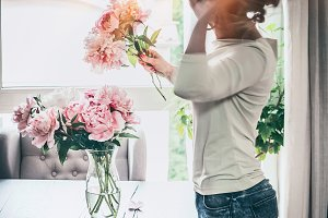Women arranging peonies at home