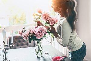 Women arranging peonies in vase