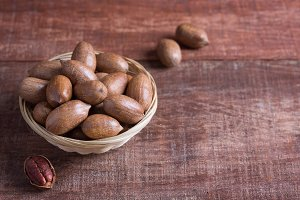 Pecan nuts in a bowl on a wooden table. Organic food for healthy eating