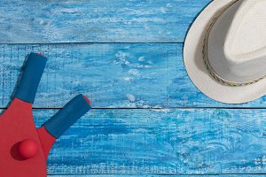 Equipment for playing beach tennis and hat on the blue wooden background