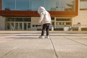 Little girl with hoodie looking her sneakers outdoors