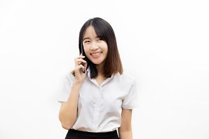 Smiling happy and cheerful Asian female formal dress holding a smart mobile phone making a phone call isolated over white background