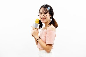Young beautiful and pretty Asian female student holding a microphone singing with attractive smile isolated over white background
