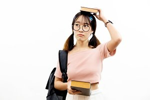 Young Asian female academic teen students with trendy eye glasses holding pile of books with bag isolated over white background