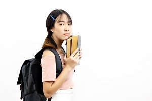Young Asian female college students holding pile of books with bag isolated over white background
