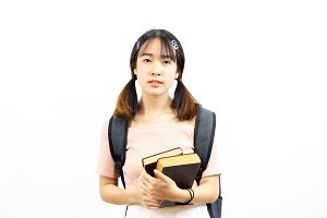 Smiling happy and casual Asian female college students holding pile of books with bag isolated over white background
