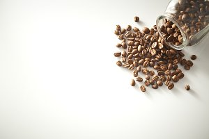roasted coffee beans poured from clear glass on white background