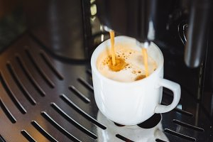 Close-up of espresso pouring into white cup from coffee machine. Professional coffee brewing