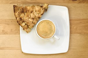 Top view of white coffee cup filled with fresh hot espresso together with peace of freshly baked homemade apple pie on a square plate on wooden background