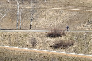 A man ride on bike on the rural road in a park at early spring time. Sport and active life concept. Hill with road at angle make beautiful lines, outdoor landscape photography