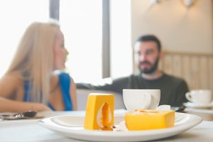 Young couple having lunch in cafe waitress passes - defocused