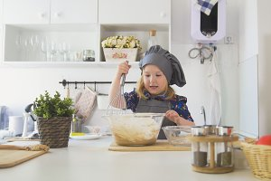 Little girl mixes the mixture for cookies with a big spoon