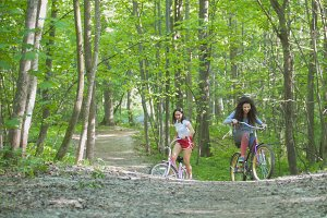 Two girls walking with bicycles in the green forest, summer day