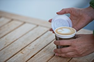 Female hands holding a paper coffee