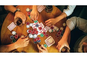 Top view photo of friends sitting at wooden table. Friends having fun while playing board game.