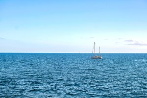 A sailboat on the horizon.