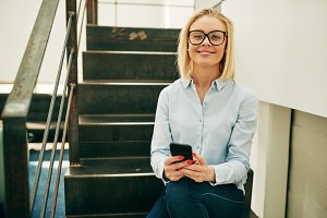 Smiling businesswoman using her cellphone while sitting on office stairs