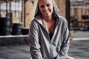 Young woman smiling confidently in a gym before working out