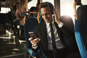 Young businessman reading texts and wearing headphones on a bus