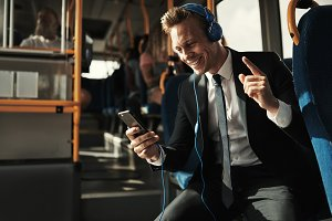 Smiling young businessman riding a bus and listening to music