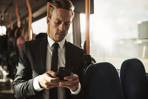 Young businessman reading texts while standing on a bus