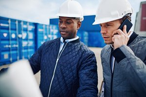 Engineers discussing building plans while standing in a container yard