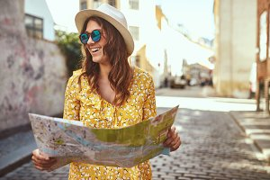 Smiling young woman exploring cobblestone streets with a map