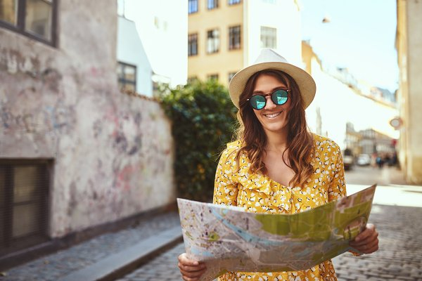 Smiling woman reading a map while w…