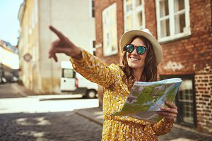Smiling young woman sightseeing in the city with a map
