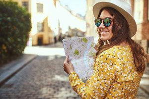 Smiling young woman enjoying the day sightseeing with a map