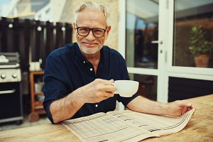 Smiling senior man reading a newspaper outside and drinking coffee