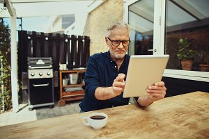 Smiling senior man using a digital tablet and drinking coffee
