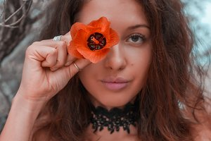 young woman holding orange flower on her eye