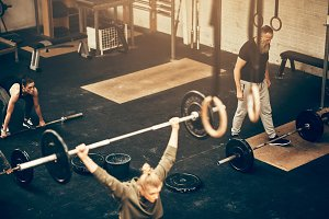 Fit people exercising with weights during a gym class
