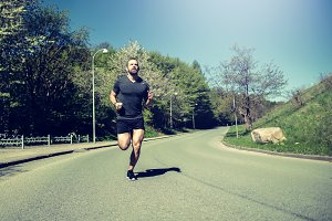Fit young man jogging alone along a country road