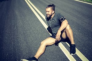 Fit young man sitting on a road relaxing after jogging