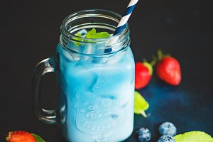 Butterfly pea tea with milk in a glass with ice