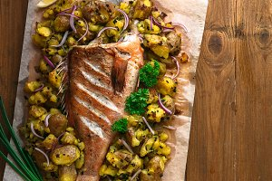 Sea perch or grouper baked with potatoes, top view, copyspace