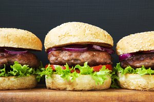 Side view burgers on wooden board.