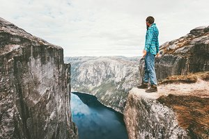 Explorer man standing on cliff