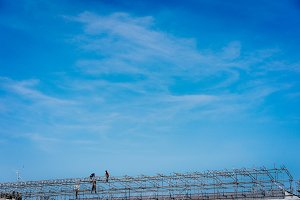 Construction workers working on scaffolding. Blue sky in background