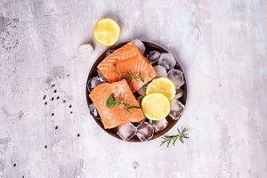 Salmon steaks on ice with lemon slice on wooden plate. Lean proteins.