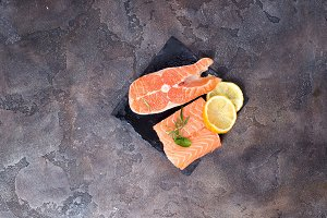 Raw salmon fillet with rosemary on stone cutting board. Lean proteins.