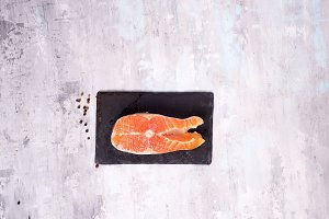 Raw salmon filet on dark slate cutting board. Lean proteins.