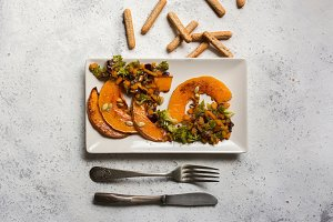 sliced baked pumpkin, with broccoli and assorted vegetables, on rectangular white plate