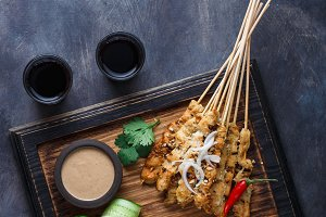 Chicken Satay or Sate Ayam - Malaysian famous food. Is a dish of seasoned, skewered and grilled meat, served with a peanut sauce. Top view copyspace