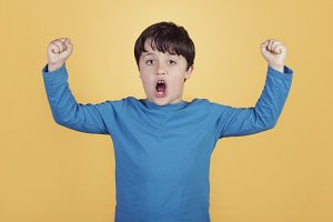 boy with hands in the air screaming