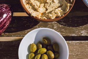 Hummus and green olives, on the table, above.